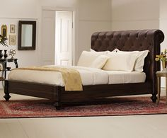 Ashe's platform bed with leather headboard. The room is simple and very masculine.