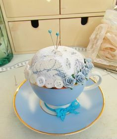 Teacup pincushion with buttons  blue roses trim.