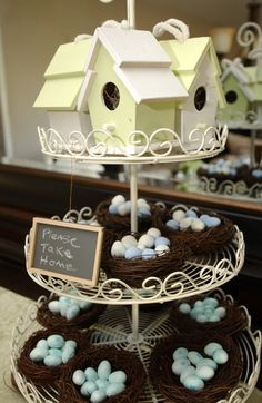 Painted birdhouses and candy filled bird nests as baby shower favors.