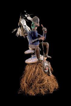 Masque d'initiation Yaka, République Démocratique du Congo. Bois, fifibre, tissu, colorants végétaux. Intéressant masque supportant, sur une tour, une marionnette en toile, ornée de plumes, tenant un… - Leclere - Maison de ventes - 25/09/2015