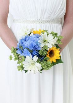 Find silk bouquets for your spring wedding like this adorable bouquet of faux yellow sunflowers, blue hydrangeas, white wildflower daisies, and green sedum accents.
