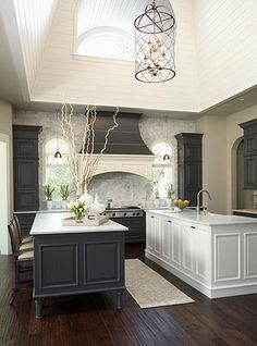 Charcoal cabinets with off-white walls, countertops, and island; also love the all stone focal wall and two tone stove vent
