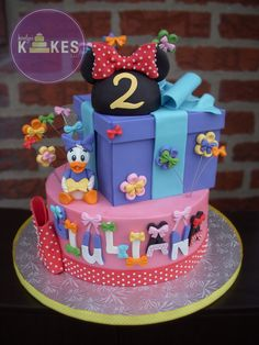 Minnie Mouse and Daisy Duck Bowtique cake Bottom cake iced in buttercream and decorated with Marshmallow Fondant (MMF).  Box is cake covered in MMF.  Minnie ears are rice cereal covered in MMF.  MMF Daisy Duck :)