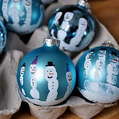 Paint their hands white and place a solid colored ornament in their hand. Each finger is a snowman decorated with permanent markers.