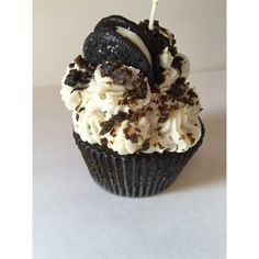 """An enticing cupcake candle. Luscious chocolate cake topped with lightly sweetened vanilla buttercream, and crushed cookie sandwich. 5 oz of scented wax - Approx. 4"""" around and 6"""" tall - Cotton core wi"""