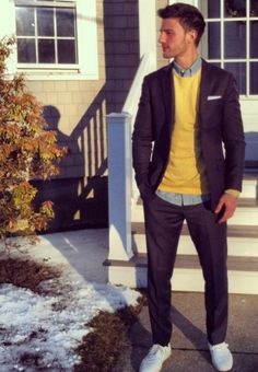 Navy suit, light chambray shirt, yellow sweatshirt, blue and white striped pocket square, and all white tennis shoes.