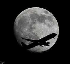An LAX bound passenger airplane drops the wheels as it crosses the moon two days before the Full Moon and Super Moon passing over Whittier, California, on its final approach to the Los Angeles Airport, on Friday, August 8, 2014