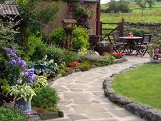 I love this flagstone walkway & flower beds!
