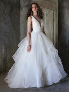 A ballgown wedding dress doesn't need bells and whistles to be fabulous. A chic fabrication and elegant draping does the trick just fine.