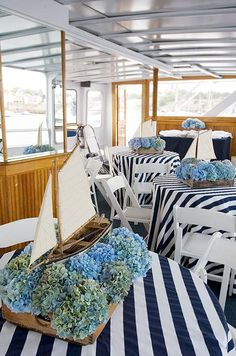 For whimsical centerpieces, model boats sail amongst blue and green hydrangeas.