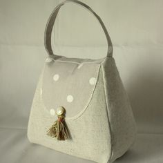 Handbag Door Stop Globaltex Fabric Dotty Taupe @Folksy: SOLD OUT. *Professionally made using a plain linen fabric *Front panel and handle in Globaltex fabric Dotty in the Taupe colourway and decorated with a small pearl button and tassle *Size Approx. Width at the base 19cm *Depth 7.5cm *Height 15cm excluding handle *Secure velcro fastening on the base...