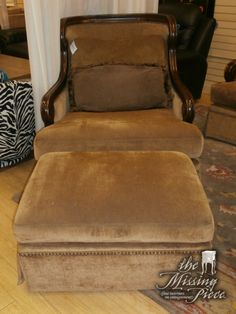 This chair and ottoman set measures 36x45x41. Covered with a soft, deep tan fabric, this chair has medium tone wooden arms and border as well as having a nailhead detail around the edges of the chair.