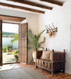 00226477. Recibidor rústico con portones con remaches, banco de madera, suelo de barro, alfombra y colgador_226477