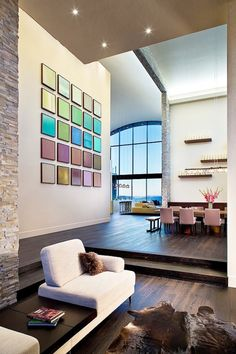 Using small canvas paintings, as in this case, can be a way to bring color into your space. Even the bright colors fit well in this room that is otherwise neutral.