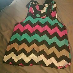 """Chevron top with bow back...adorable! NEVER WORN! I bought this off of zulily and it does not fit me, so it's never been worn. It's sheer 100% polyester with an adorable black bow on the upper back of the tank. I LOVE this top and was sad their sizing is way off. Tag says 3x but it would fit an XL. So I took measurements. When i lay the shirt flat the chest is 23"""", the bottom hem is around 27"""", and when I measured from the top of the tank strap to the bottom it measures 25"""" on the front and…"""
