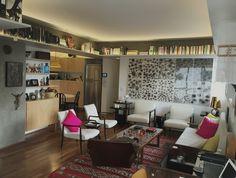 Sala de estar na Vila Madalena. Esse apartamento respira arte. Piso de madeira, concreto aparente, prateleiras, decoração colorida, organização de livros, marcenaria em compensado naval. Puro amor! Living room and home decor.
