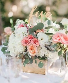 A clear cylinder vase flled with cream hydrangeas, coral spray roses, silver dollar eucalyptus grey dusty miller, and seeded eucalyptus surrounded by gold mercury glass votives