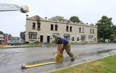 Owen Sound firefighter Jay Forslund rolls up hose Monday after he and members of three fire departments battled several blazes in the city early Monday morning. The 10 plex, background, is among seven fire scenes being investigated by police and the Ontario office of the Fire Marsha. Fifteen families were left homeless. (James Masters/Owen Sound Sun Times/Postmedia Network)