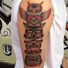 What does totem tattoo mean? We have totem tattoo ideas, designs, symbolism and we explain the meaning behind the tattoo. Totem Tattoo, Tiki Tattoo, Native Tattoos, Tribal Tattoos, Tatoos, Upper Arm Tattoos, Arm Tattoos For Guys, Totum Pole Tattoo, Teardrop Tattoo