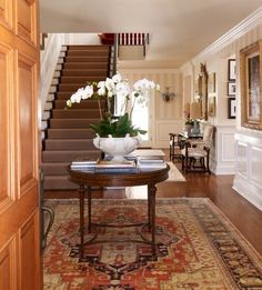 Beautiful entry.....rug, wainscoting, rug, wood floor, furniture, art, all of it really (Far Hills Family Home)