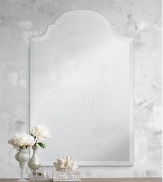 Frameless mirror on wallpapered wall with shells and flowers