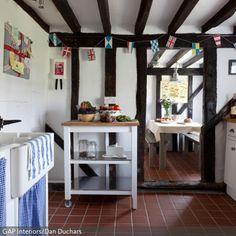 Die Küche im Fachwerkhaus erweckt die ländliche Idylle zum Leben. Durch Küchentücher und Vorhänge in Blau erhält es einen maritimen Look. - mehr auf www.roomido.com