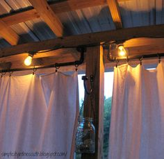 How to make curtain rods from galvanized plumbing parts. Drop cloth curtains and string lights for the porch.