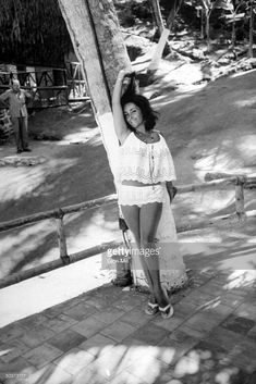 Actress Elizabeth Taylor posing in bathing suit on location during filming of motion picture The Night of the Iguana.