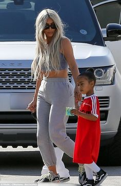 Mommy's girl: North was enjoying a snack while heading with mom Kim and son Saint...