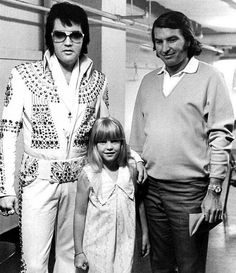 """Seattle in April 1973. Photo: Ed Bonja   Elvis, Tina Hulett and Tom Hulett, Ex-Quarterback, Leading Concert Promoter  """"For Presley, Mr. Hulett managed every performance from 1969 until Presley died. He was invaluable to Concerts West because of his ability to deal with Presley's manager, Col. Tom Parker,""""   10/2016 - At the EPE Auction at the Grand Opening of The Guest House at Graceland, the TCB Necklace Given by Elvis Presley to Tour Promoter Tom Hulett sold for $10,000   Hulett died in…"""