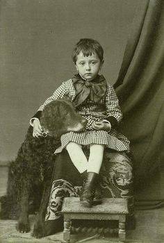 Vintage photo, sad-looking kid on seat, curly-haired dog with his head on his lap