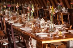 classic barn wedding with farm tables, assorted vintage wooden chairs and vintage china at The Inn at West Settlement