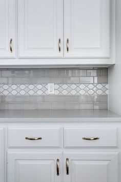 grey and white kitchen. White cabinets with grey subway tile and a decorative glass liner. Grey island. Casesarstone Quartz countertops in London Gray