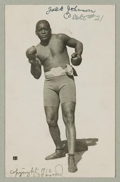 [Jack Johnson, full-length portrait, standing facing front, wearing boxing shorts and boxing gloves] 1910