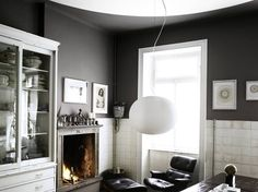Glo Ball S designed by Jasper Morrison for FLOS enhances the contemporary aesthetic of this living room featuring a built in fireplace, dark gray walls, black modern seating and unique wall decor.