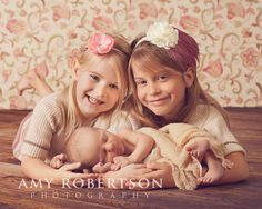 siblings and newborn picture pose idea. The girls on their belly and Hudson laying in front of them.