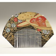"Japanese lacquer hair comb; carved fan form with raised gilt enameled boat motif, red accents and mother of pearl floral inlay on black lacquer ground. 2 1/8"" x 3 3/8""."