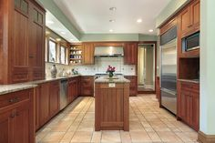 Sand colored tile floor helps make the naturally dark wood cabinets pop in this lengthy kitchen.