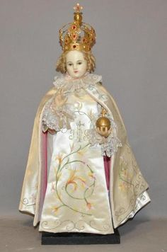 Enfant Jésus de Prague en cire, la couronne en métal doré et pierres de couleurs, il est vêtu d'une tunique soie et dentelle et motifs à la gouache. (très frais). H. 54cm.