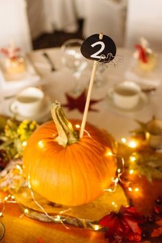 Chalkboard-style table numbers displayed with pumpkins {Will Pursell Photo}