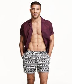 Patterned swim shorts with an elasticized drawstring waistband. Side pockets, welt back pocket with Velcro fastener, and mesh liner shorts.