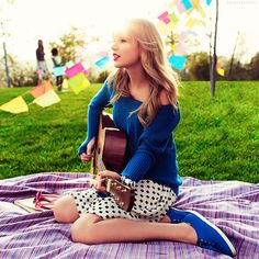 Taylor Swift. Kinda obsessed with this picture...she's just chilling in the park with her guitar and some random flags in the background.