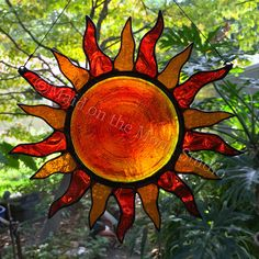 Stained glass sunburst - light orange rays with orange & yellow rondelle center - Maid on the Moon Studio