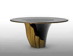 Dining Table YASMINE I Yasmine brings a chic and sexy round dining table with a contemporary design that will catch your eyes immediately. The sultry silhouette is fashioned from tailored glass and mounted on a solid wooden base. Classic black lacquer and luxurious gold intermix arching back and forth to reveal each color's respective dominance in the design. The combination Black and Gold is certainly lethal and brings luxury and elegance to this beautiful round dining table.