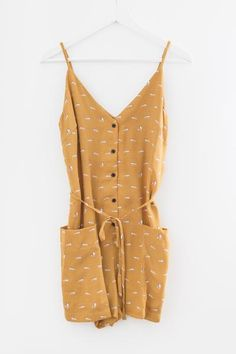Mustard fox printed romper V neckline and back Button-up front Spaghetti straps Large front pockets Bow-tie strap around waist Non-stretch woven material 100%