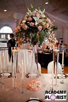 Gorgeous cascading centerpiece in clarinet vase. Filled with a stunning assortment of lilies, roses, and orchids with gold ribbon - vase turned upside down - filled with rose petals at base - interested take Created by Florist Beautiful Bouquet Of Flowers, Peach Flowers, All Flowers, Wedding Flowers, Wedding Centerpieces, Wedding Decorations, Table Decorations, Perfect Wedding, Our Wedding
