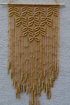 Wall panels handmade macramé technique. Material: 100% polyester. Color: gold Strap: natural wood - pine. Dimensions: The length of the wooden strap to the bottom, including the thread - 81cm / 31,9 inches Width - 36cm / 14.2 inches