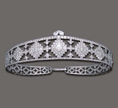 AN ELEGANT ART DECO NATURAL PEARL AND DIAMOND BANDEAU, BY CARTIER The openwork old European-cut diamond tapering band, of geometric design, centering upon a pearl, measuring approximately 13.10 mm, enhanced by two pear-shaped diamonds, mounted in platinum, circa 1924 Signed Cartier,