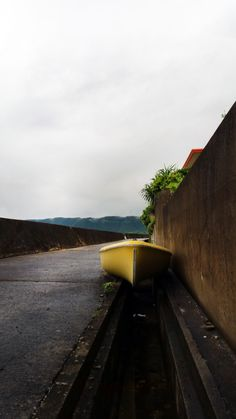 yellow boat on the dark concrete walls of the volcanic island Amami Oshima