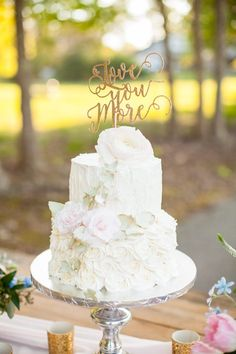 White wedding cake with floral and icing embellishment https://www.thecelebrationsociety.com/weddings/glam-country-wedding-inspiration-barn-oak-manor-newnan-ga/
